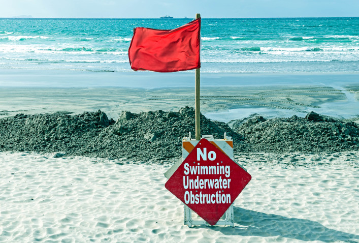 Red flag and warning sign on beach in Coronado CA