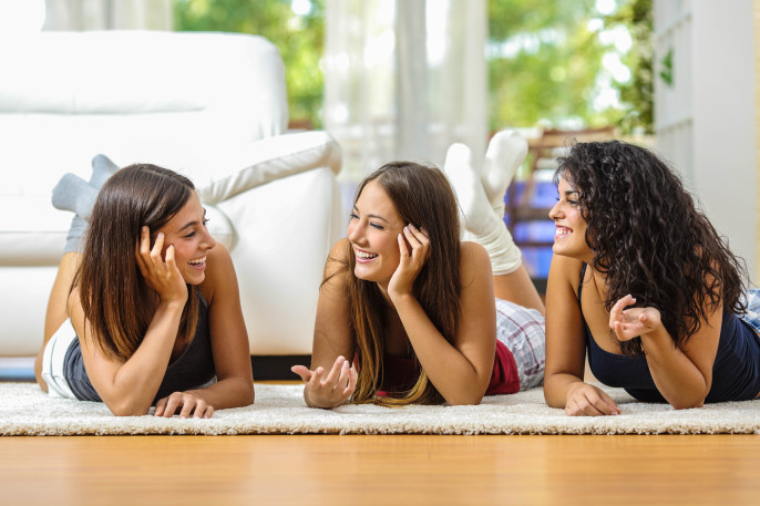 Group of happy teen friends talking lying on the floor at home shutterstock_323664887-2