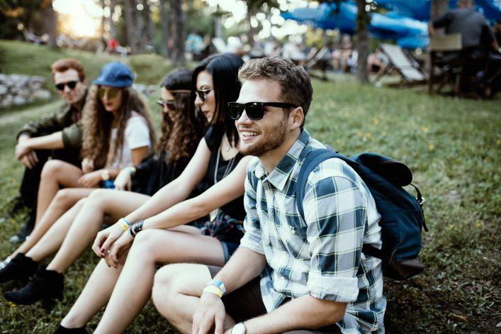 Eine Gruppe junger Leute sitzt bei einem Festival im Gras.