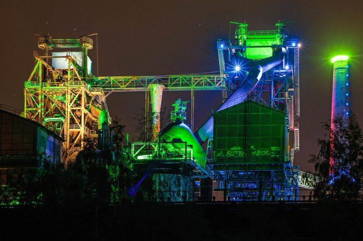 Der Landschaftspark Duisburg-Nord wird bei Nacht in bunten Farben angestrahlt.