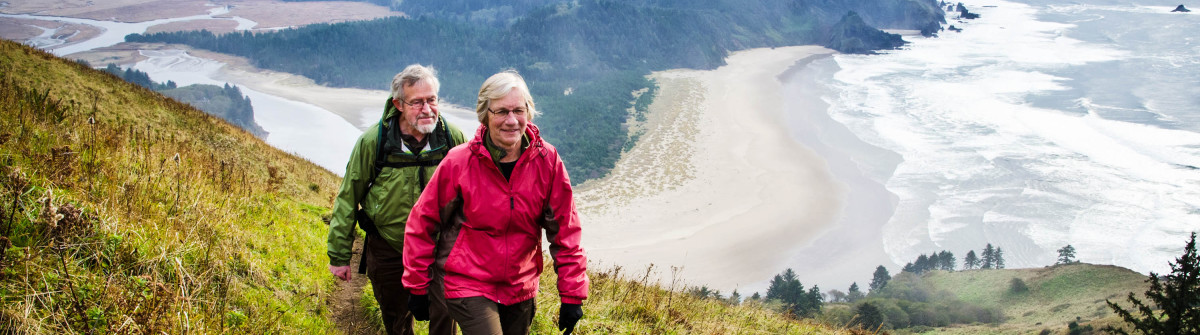 Senior couple hiking above coast