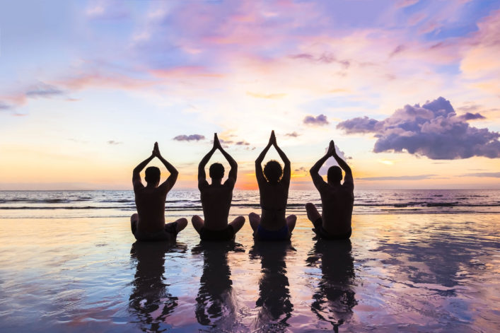 Group of four people practicing meditation and yoga on the beach at sunset shutterstock_512058763-2