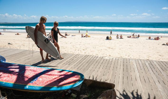 Young folk carrying surfboard, walking and talking, Noosa, Queensland, Australia.