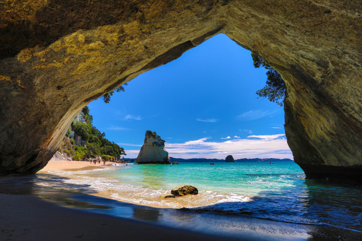 View of Cathedral Cove looking out onto ocean and blue sky