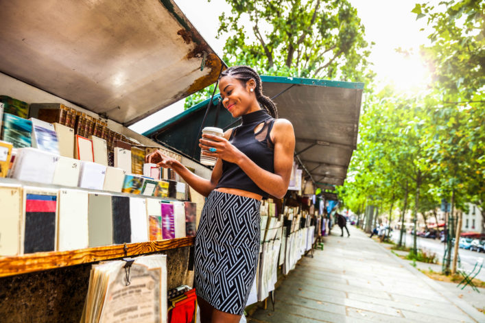 Young woman looking for books in a kiosk in Paris