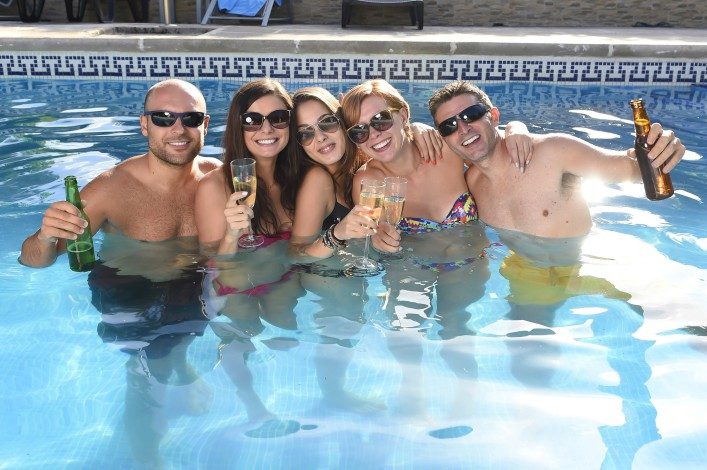 happy attractive friends at hotel resort swimming pool drinking beer