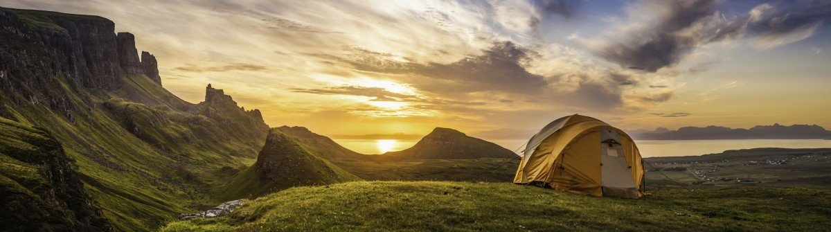 Golden sunrise illuminating tent camping dramatic mountain landscape panorama Scotland