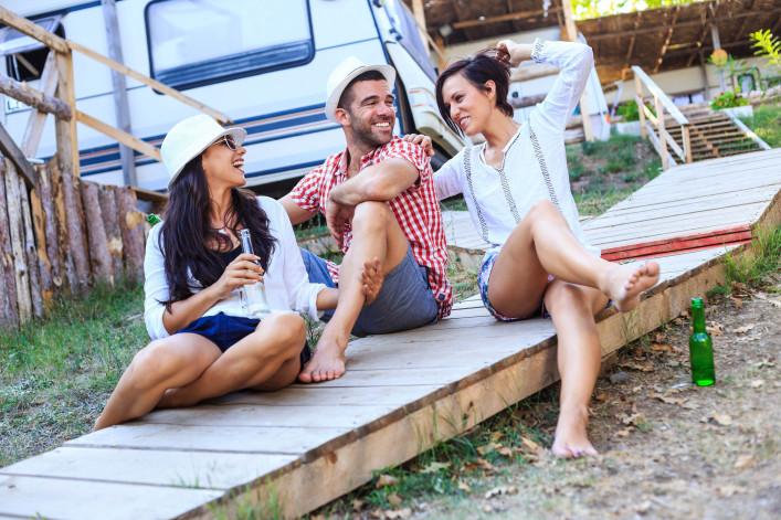 Young people having fun near the caravan