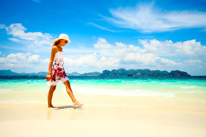 Young woman in dress and straw hat walking on beach shutterstock_73201333-2
