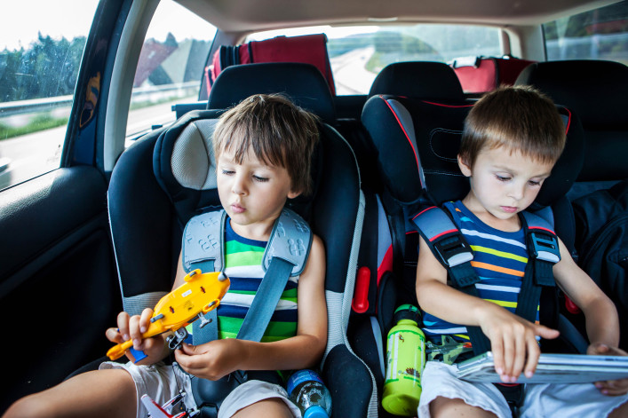 Two boy in car seats, traveling in car and playing