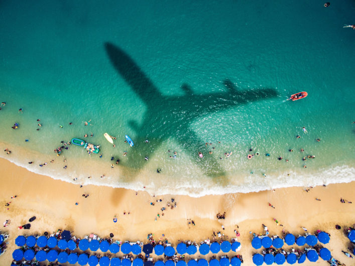Airplane's shadow over a crowded beach