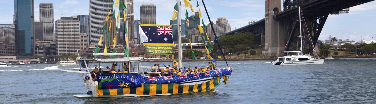 Decorated yacht sails under Sydney Harbour Bridge on Australia D