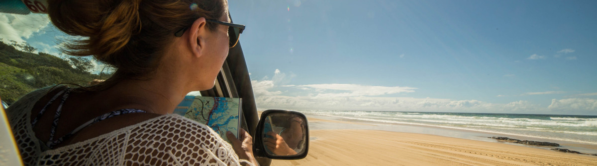 Young woman in 4×4 reads a road map, Fraser Island