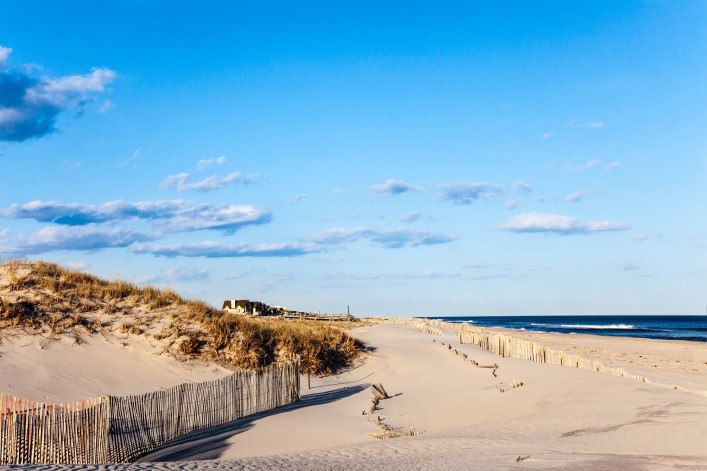 Beach Fence, Sand, Houses and the Ocean.