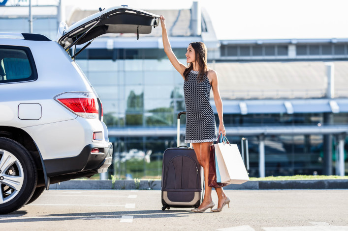 Cheerful woman is standing near her car and closing the trunk shutterstock_316213874-2