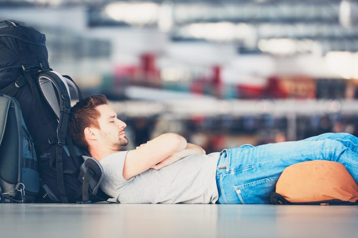 Man sleeping at the airport shutterstock_585257939