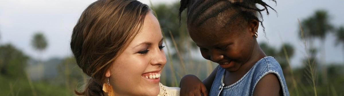 Amerikanische Frau hält Afrikanische Mädchen iStock_000014772638_Large_1920
