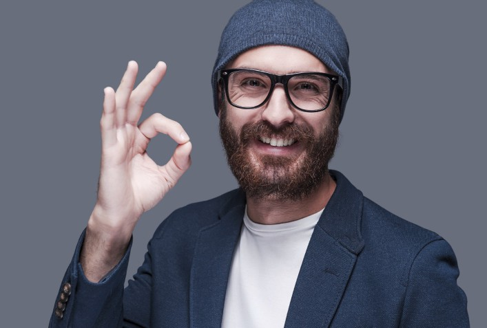 Everything is OK. Handsome young bearded man gesturing OK sign and smiling while looking at camera and standing against grey background