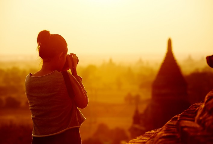 female traveler photographing temples at Bagan Myanmar Asia at sunrise shutterstock_134373716