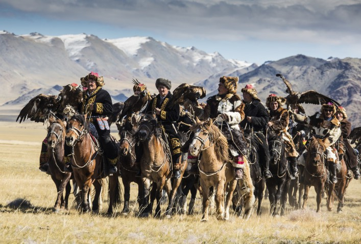 Mongolian eagle hunters riding to the festival iStock_000022566180_Large EDITORIAL ONLY Josef Friedhuber