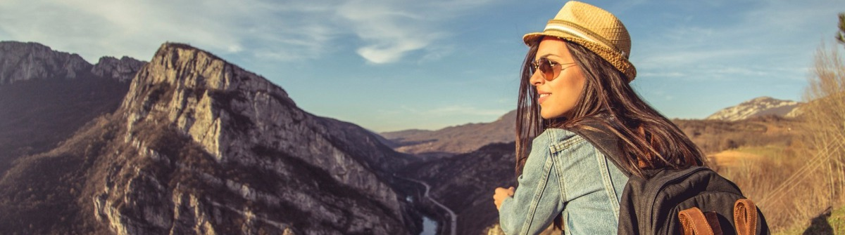 Hiker sits on edge of the cliff and enjoying sunlight