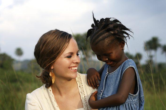 Eine amerikanische Frau hält ein afrikanisches Baby auf dem Arm.