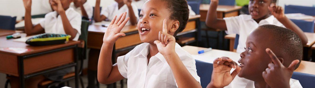 Afrikanische Kinder melden sich begeistert in einer Schulklasse.
