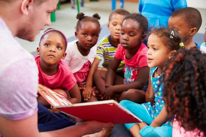 Ein junger Mann zeigt einigen kleineren Kindern ein Buch.