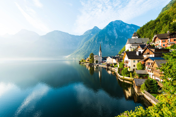 First of the early morning sunlight and mist fall on the lakeside village of Hallstatt, Austria
