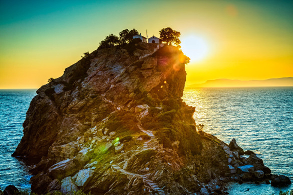 Rock with famous church Agios Ioannis Kastri on Skopelos island, Greece at sunrise, where scenes of Mamma Mia! movie were filmed. Sun raises above Alonissos island.