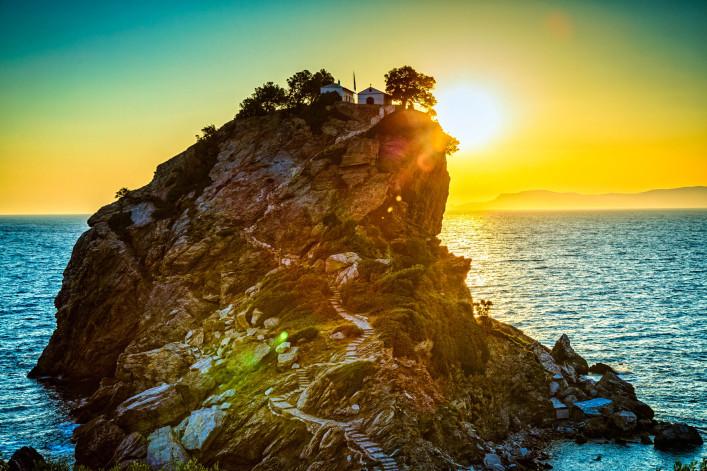 Rock with Agios Ioannis church on Skopelos island at sunrise