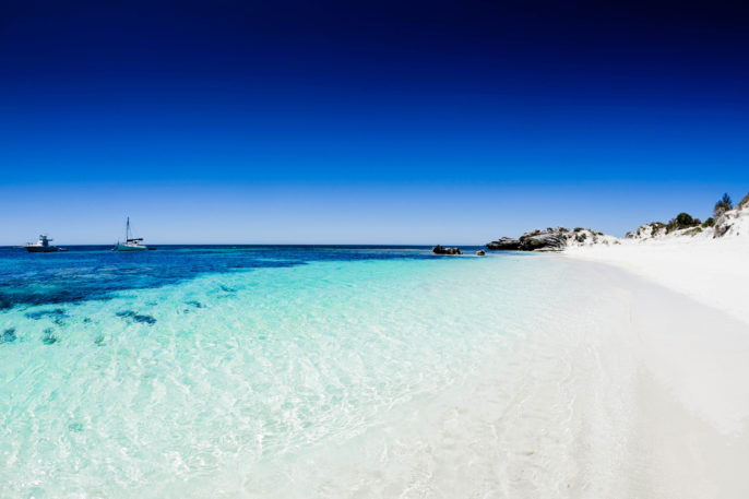 Beach with white sand and clear blue water and sky
