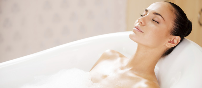 Beauty in bubble bath. Side view of attractive young woman keeping eyes closed while enjoying luxurious bath