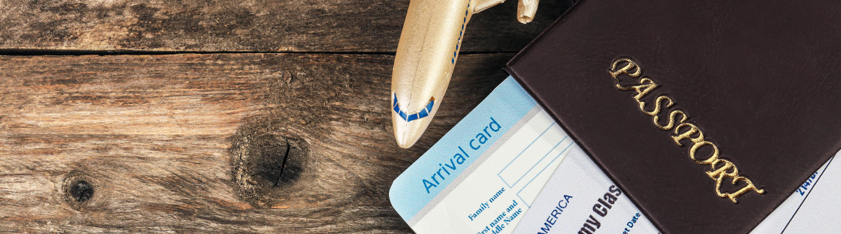 Airline tickets and documents on wooden background shutterstock_269588303-2