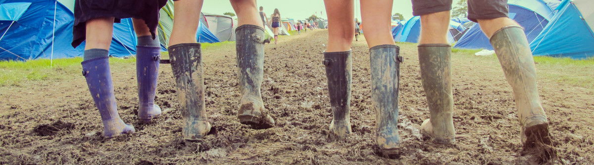 Close up of friends walking through a muddy campground