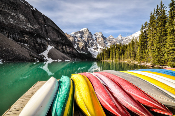 Coloured canoes at lakeside.