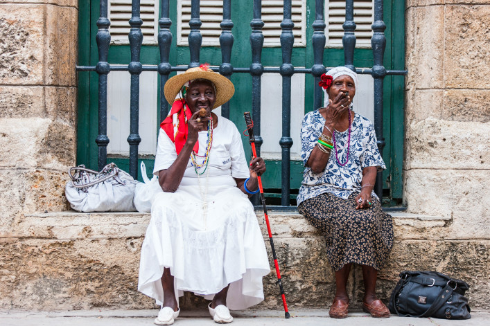 Cuban ladies dressed in typical clothes posing for photos while smoking a huge cuban cigars in Havana, Cuba shutterstock_331689242 EDITORIAL ONLY BlueOrange Studio-2