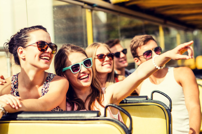 group of smiling friends traveling by tour bus shutterstock_281448020-2