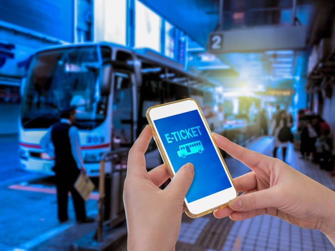 Hand holding mobile phone with E-Ticket word with blur bus terminal background shutterstock_360686624-2