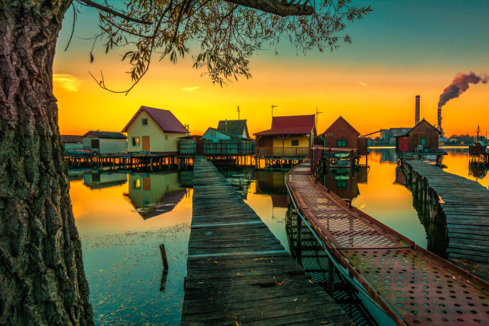 Small fishing cottages in the sunset on Bokod lake in Hungary shutterstock_334452209-2