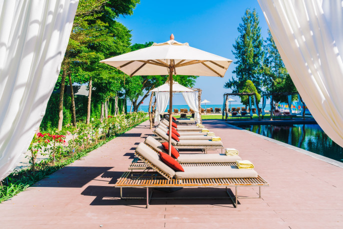 Umbrella pool and chair in beautiful luxury hotel pool resort – Filter Processing style pictures shutterstock_378577537-2