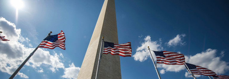 Low view of the Washington Monument with flags in front
