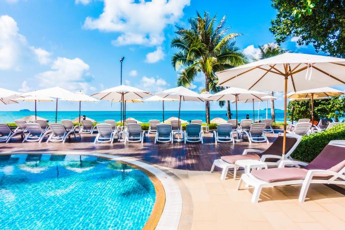 Beautiful luxury umbrella and chair around outdoor swimming pool in hotel resort shutterstock_420110824-2