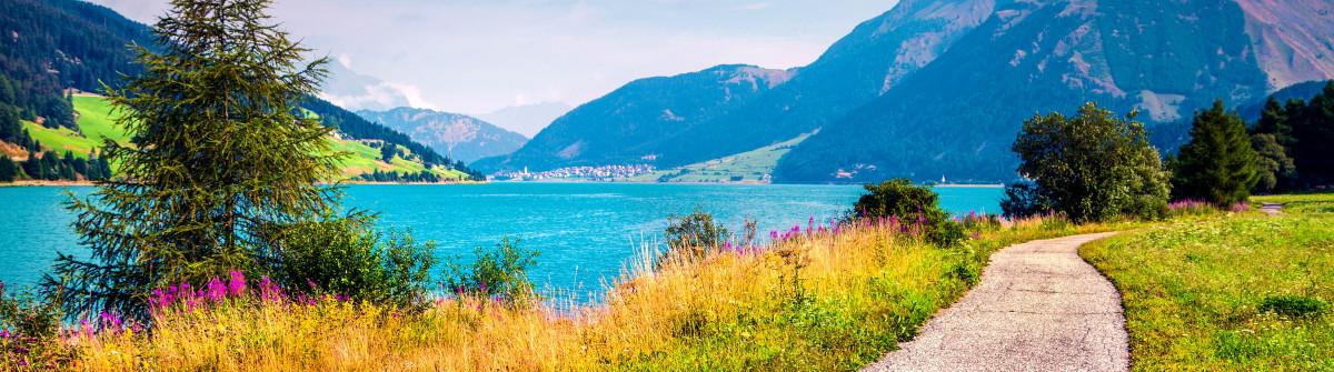 Die Fahrradwege schlängeln sich um den Reschensee in Südtirol.