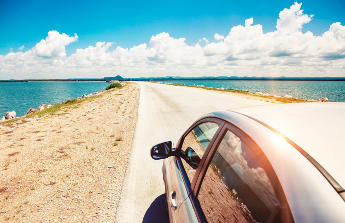Car driving across ocean by the road shutterstock_141621238-2