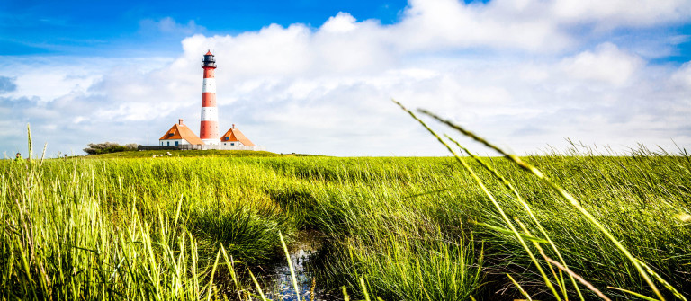 Beautiful view of landscape with small pond and lighthouse in th