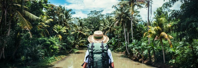 Traveling woman with backpack and straw hat looking at tropical river at sunny day shutterstock_400843174-2