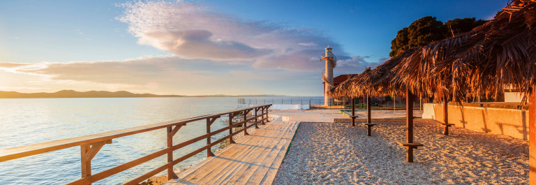 Wooden walkway leading to a lighthouse in Zadar, Croatia
