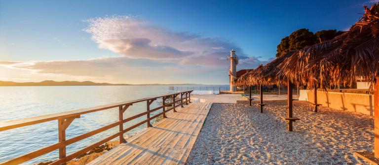 Wooden walkway leading to a lighthouse in Zadar, Croatia