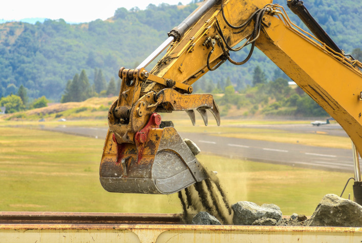 A large tracked hoe or excavator working at a construction site to extend an airport runway shutterstock_108570776-2